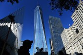 People walk past the construction site of the One World Trade Center in New York on October 17 2014 US spending on construction slowed in August 2014...