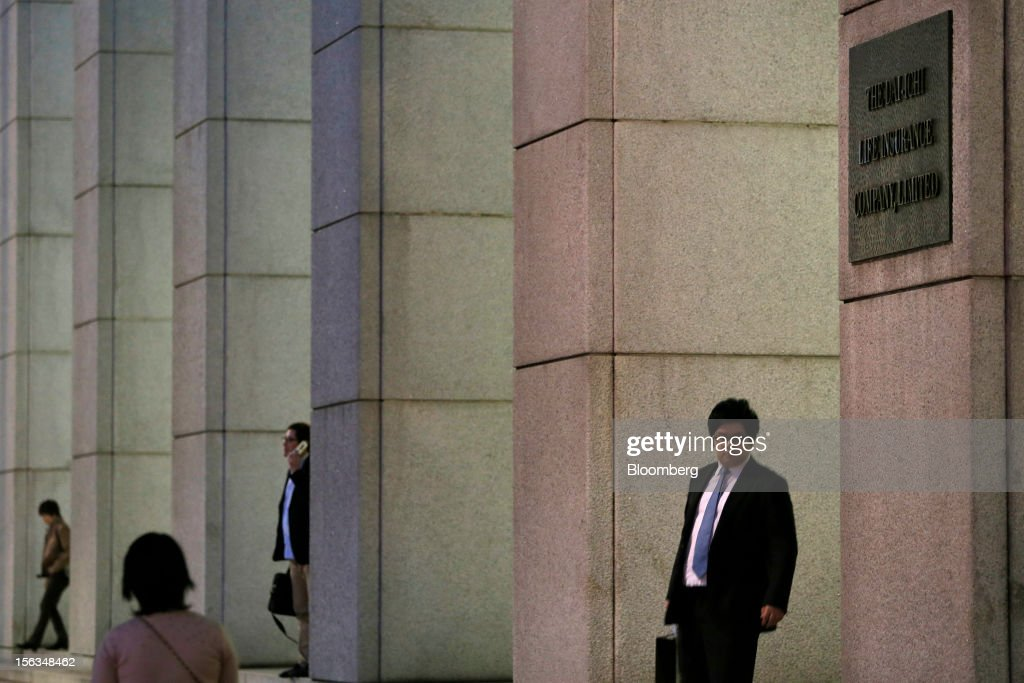 People walk past the Dai-Ichi Life Insurance Co. headquarters in Tokyo, Japan, on Tuesday, Nov. 13, 2012. Dai-Ichi Life is scheduled to announce first-half earnings results on Nov. 14. Photographer: Kiyoshi Ota/Bloomberg via Getty Images