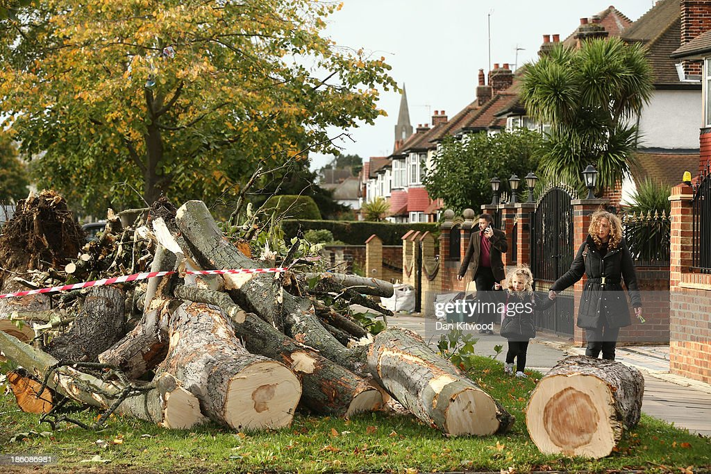 People walk past the debris of fallen trees in Bath Road, Hounslow on October 28, 2013 in London, England. A fallen tree has caused a devastating gas explosion in west London, destroying three homes Approximately 220,000 homes are without power and two deaths have been recorded after much of southern England has been affected by a severe storm. Transport links on road, rail, air and sea have been severely disrupted by hurricane-force winds that have almost reached 100 mph in places.