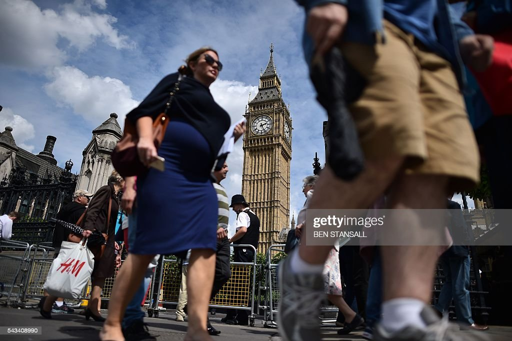 People walk past and the Big Ben clock face on the Elizabeth Tower (C) in the Palace of Westminster in central London on June 28, 2016. EU leaders attempted to rescue the European project and Prime Minister David Cameron sought to calm fears over Britain's vote to leave the bloc as ratings agencies downgraded the country. Britain has been pitched into uncertainty by the June 23 referendum result, with Cameron announcing his resignation, the economy facing a string of shocks and Scotland making a fresh threat to break away. / AFP / BEN