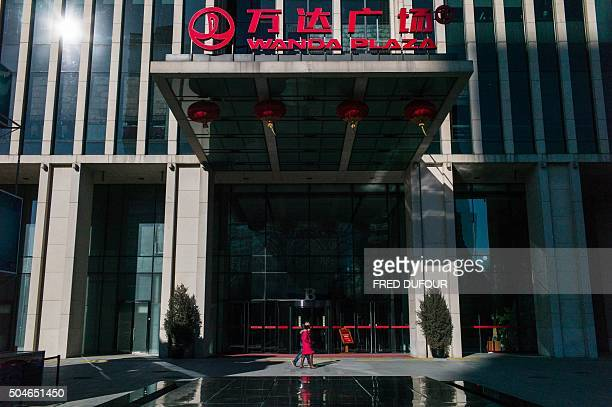 People walk past the entrance of the Chinese conglomerate Wanda Group building in Beijing on January 12 2016 Chinese conglomerate Wanda Group is...