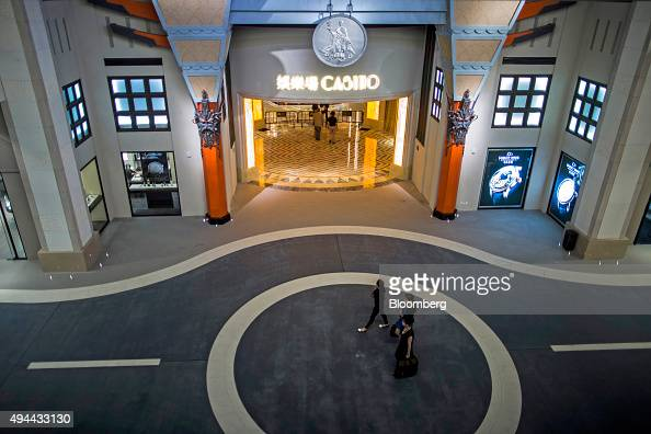 People walk past the entrance to the casino floor on The Boulevard at Studio City casino resort developed by Melco Crown Entertainment Ltd in Macau...
