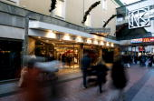People walk past the entrance to the luxury shopping mall NK where Lisa Persdotter and Charles Simonyi have made a wedding list of gift ideas for...