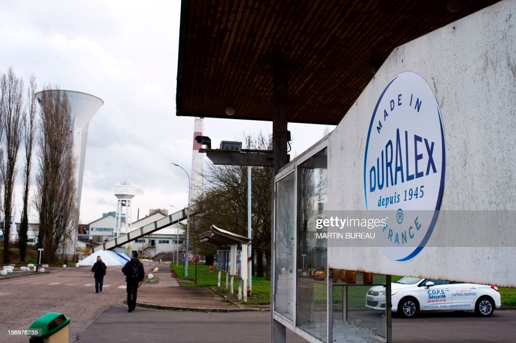 People walk past the factory of French manufacturer of glassware Duralex on November 26, 2012 in La Chapelle-Saint-Mesmin. AFP PHOTO/ MARTIN BUREAU