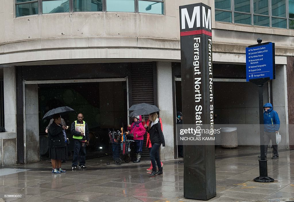 People walk past the Farragut North Metro station in Washington, DC, on May 6, 2016. / AFP / NICHOLAS