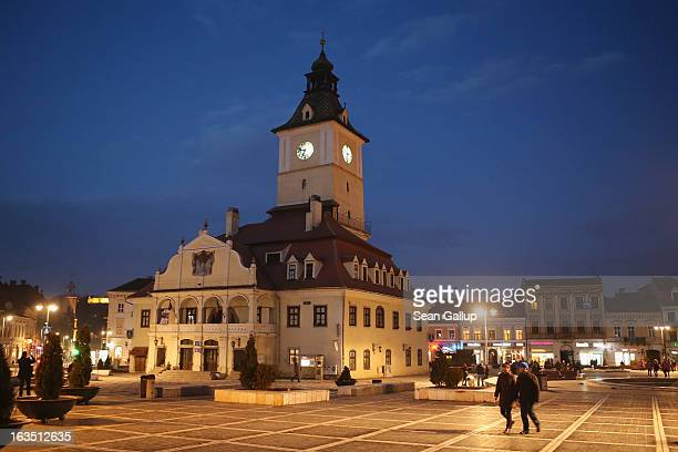 People walk past the former Council House built in 1420 in Sfatului square on March 9 2013 in Brasov Romania Brasov in German called Kronstadt was...