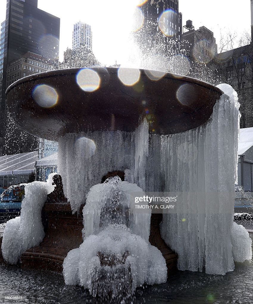 People walk past the fountain at Bryant Park in New York on January 25, 2013 as the arctic air has turned the fountain into an ice sculpture. The fountain was installed at the east side of Bryant Park in 1913 and then in 1936 was moved to the west side of the park.