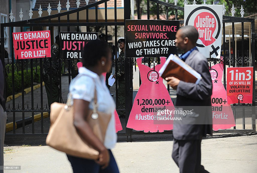 People walk past the gate of Kenya's Inspector General, bearing posters left by several hundred Kenyan protestors marching towards the police headquarters on October 31, 2013 in Nairobi, to deliver a petition of over a million names demanding justice after men accused of brutally gang raping a schoolgirl cut grass as punishment. The ferocious attack on the teenage girl and lack of action against those who carried it out has sparked outrage in the country. The 16-year-old, known by the pseudonym Liz, was reportedly attacked, beaten and then raped by six men as she returned from her grandfather's funeral in western Kenya in June, before the gang dumped her, bleeding and unconscious, in a deep sewage ditch.