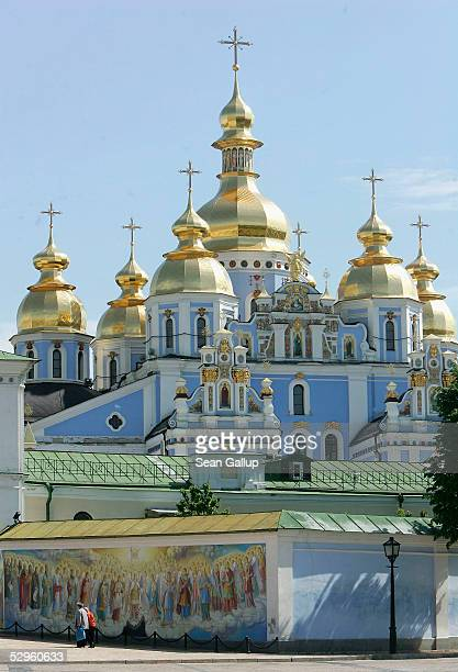 People walk past the golden towers of St Michael's monastery on May 18 2005 in central Kiev Ukraine St Michael's was destroyed in the 1930s under the...