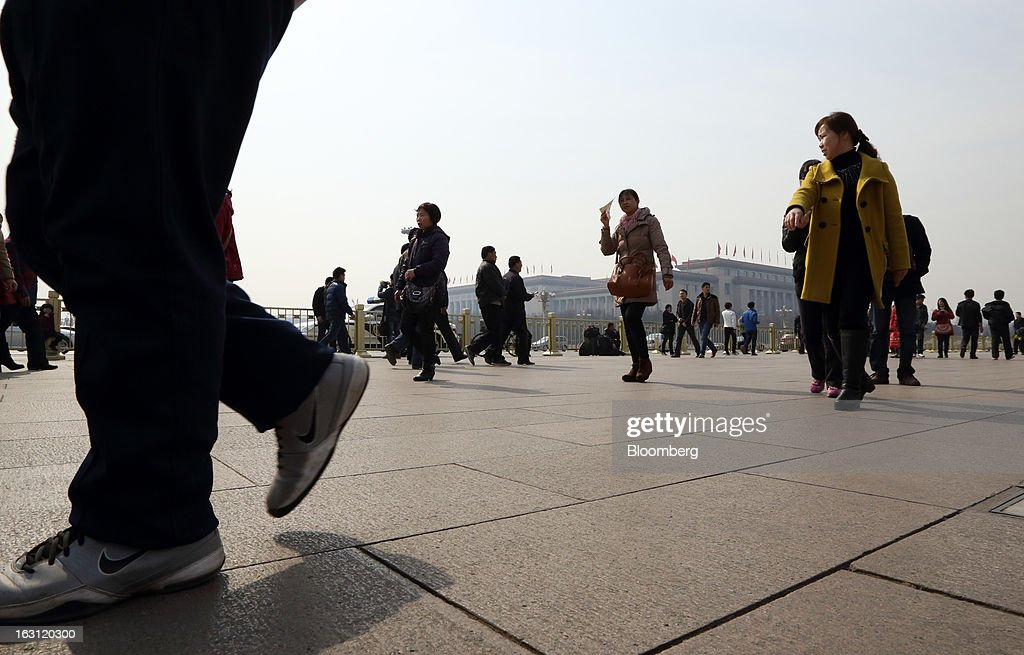 People walk past the Great Hall of the People in Beijing, China, on Tuesday, March 5, 2013. China maintained its economic-growth target at 7.5 percent for 2013 while setting a lower inflation goal of 3.5 percent, setting up a challenge for new leaders to keep prices in check without harming expansion. Photographer: Tomohiro Ohsumi/Bloomberg via Getty Images