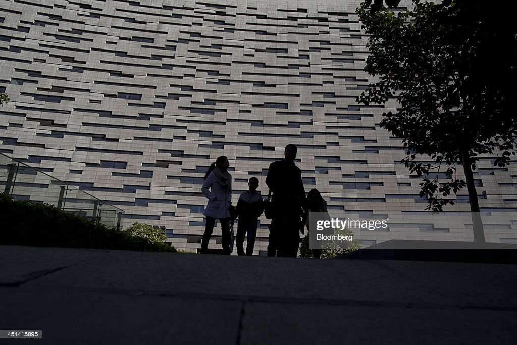 People walk past the Guangzhou library building in Guangzhou, Guangdong province, China, on Friday, Nov. 29, 2013. China is proposing the largest package of economic reforms since the 1990s to stoke growth in the worlds biggest emerging market. Photographer: Brent Lewin/Bloomberg via Getty Images