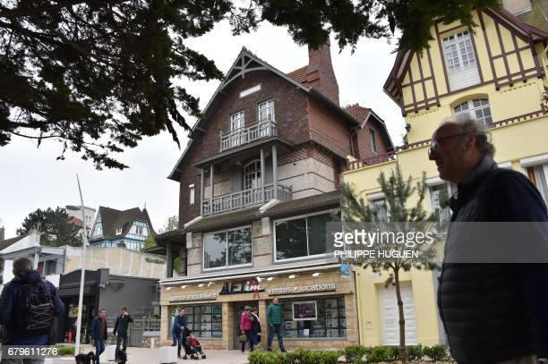 People walk past the house of French presidential candidate for the En Marche movement Emmanuel Macron in Le Touquet northern France on May 6 on the...