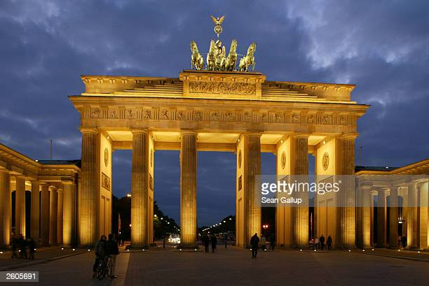 People walk past the illuminated Brandenburg Gate October 16 2003 in Berlin Germany The Brandenburg Gate which once stood just behind the Berlin Wall...