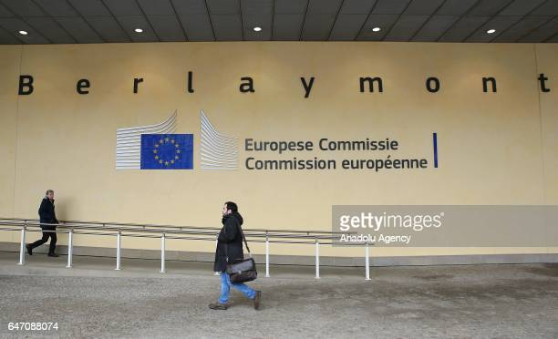 People walk past the logo of Berlaymont Building in Brussels Belgium on March 02 2017