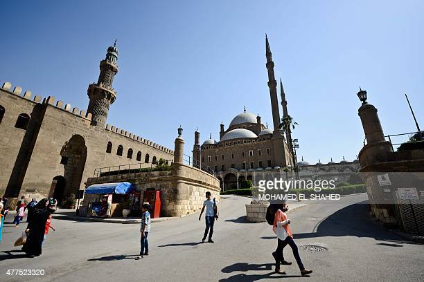 People walk past the Mohammed Ali mosque inside the Salaheddine Citadel in the Egyptian capital Cairo on June 17 2015 AFP PHOTO / MOHAMED ELSHAHED
