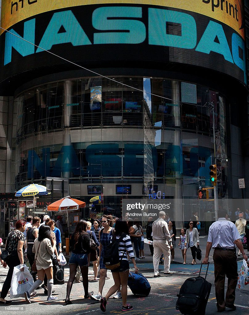 People walk past the Nasdaq exchange in Time Square on June 7, 2012 in New York City. The Nasdaq announced that they plan to set aside $40 million to handle legal proceedings surrounding the recent Facebook IPO.