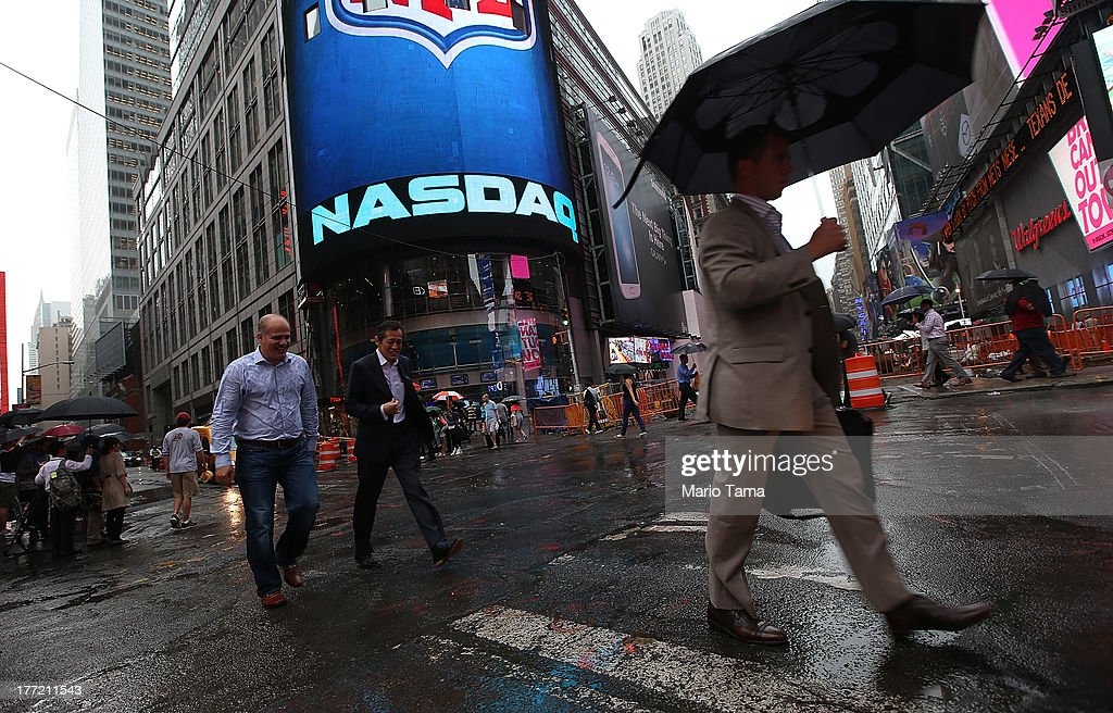 People walk past the NASDAQ MarketSite in Times Square after trading was halted on all Nasdaqlisted stocks on August 22 2013 in New York City A...
