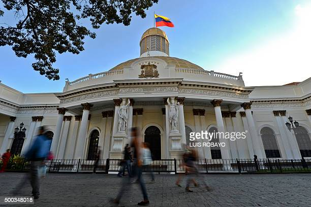 People walk past the National Assembly building in Caracas on December 7 2015 Venezuela's jubilant opposition vowed Monday to drag the oilrich...