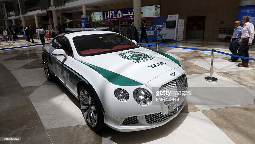 People walk past the new Dubai police Bentley patrol car on display during the Arabian Travel Market (ATM) at the Dubai World Trade Centre in the Emirati city on May 6, 2013. Dubai police have introduced top end sports cars to their patrol fleet to further strengthen the image of 'luxury and prosperity' of the Emirate.