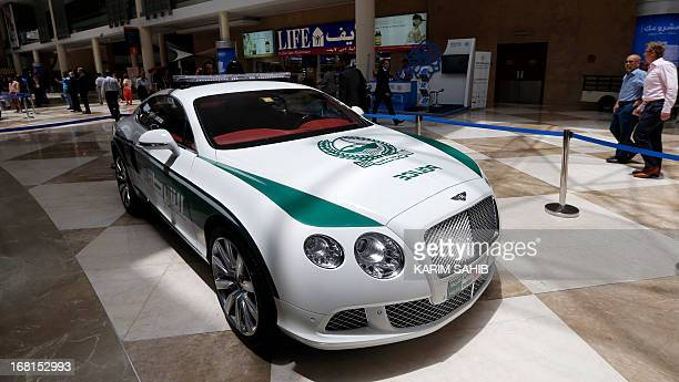People walk past the new Dubai police Bentley patrol car on display during the Arabian Travel Market at the Dubai World Trade Centre in the Emirati...