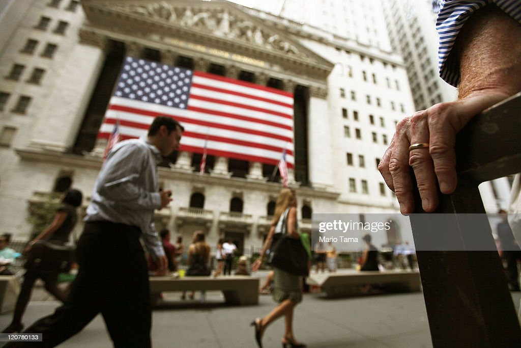 People walk past the New York Stock Exchange during afternoon trading on August 10, 2011 in New York City. Stocks fell sharply again today after a major rebound yesterday.