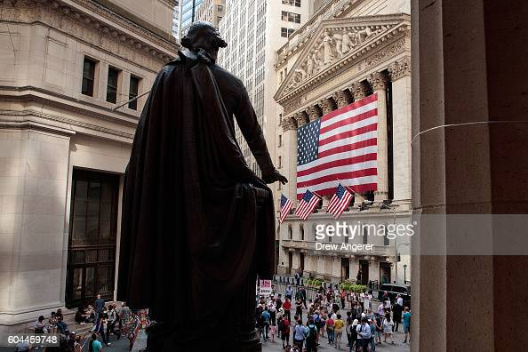 People walk past the New York Stock Exchange September 13 2016 in New York City The Dow Jones industrial average fell 258 points on Tuesday