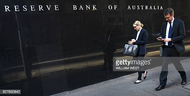 People walk past the Reserve Bank of Australia building in Sydney on May 3 2016 Australia's central bank on May 3 cut its cash rate by 25 basis...