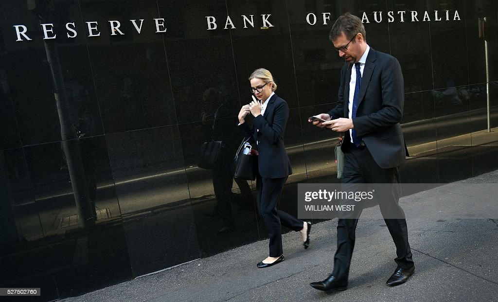 People walk past the Reserve Bank of Australia building in Sydney on May 3, 2016. Australia's central bank on May 3 cut its cash rate by 25 basis points to a historic low of 1.75 percent, with the move triggered by lower-than-expected inflation. / AFP / WILLIAM