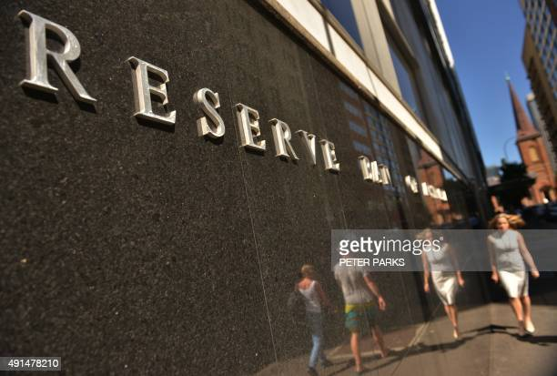 People walk past the Reserve Bank of Australia in Sydney on October 6 2015 The Reserve Bank of Australia kept interest rates at a record low of 20...