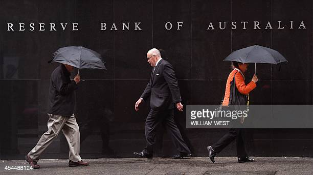 People walk past the Reserve Bank of Australia sign in Sydney on September 2 as Australia's central bank kept interest rates on hold at a record low...