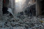 People walk past the rubbles as Russian airstrikes pound residential areas at opposition controlled Salihin neighborhood of Aleppo Syria on February...