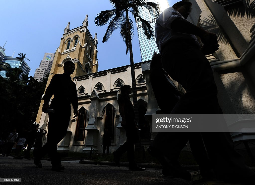 People walk past the Saint John's Anglican church after a rememberance service for the 38 victims of a ferry collision in Hong Kong on October 4 2012...