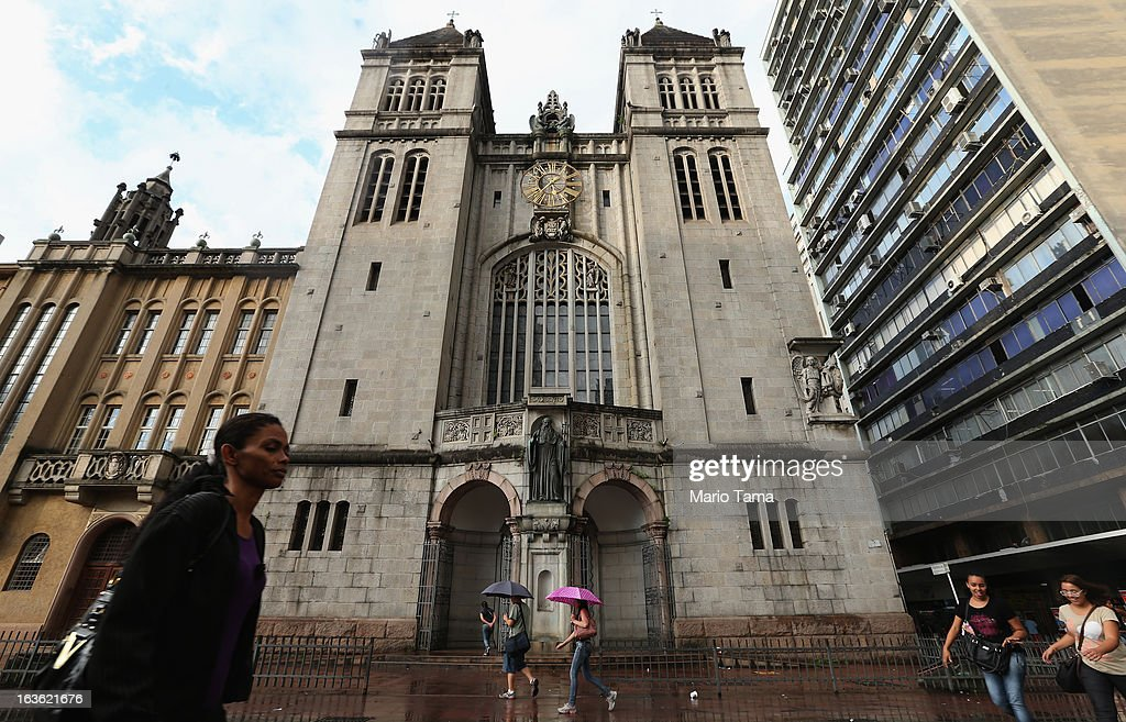 People walk past the Sao Bento Monastery following the election of the new pope on March 13, 2013 in Sao Paulo, Brazil. Cardinal Jorge Bergoglio of neighboring Argentina was elected as the first pope from South America. Brazil has more Catholics than any country in the world.