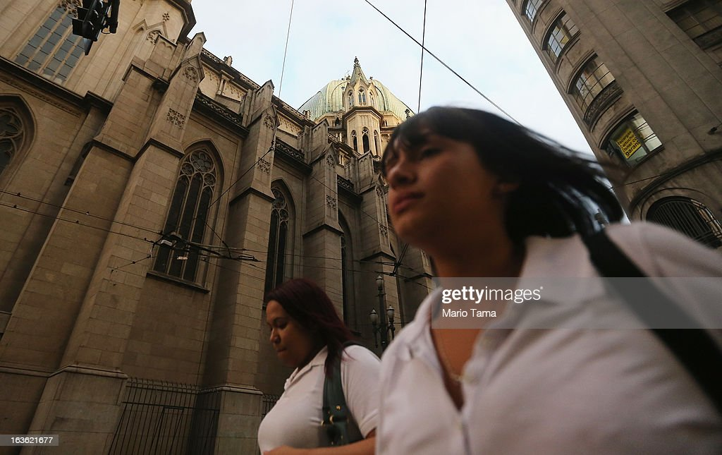 People walk past the Se Cathedral, the cathedral of the Roman Catholic Archbishop of Sao Paulo, Cardinal Odilo Pedro Scherer, after the election of the new pope at the Vatican on March 13, 2013 in Sao Paulo, Brazil. Cardinal Jorge Bergoglio of neighboring Argentina was elected as the first pope from South America. Brazil has more Catholics than any country in the world.