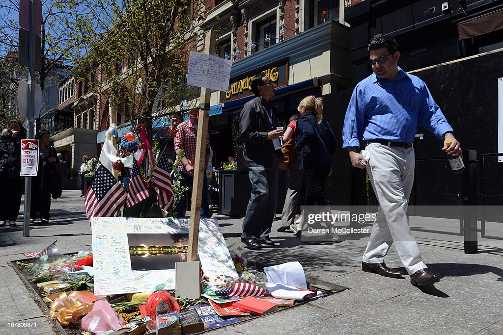 People walk past the site of the second bombing from the deadly attacks on the Boston Marathon on Boylston Street April 30, 2013 in Boston, Massachusetts. Boston continues to return to normalcy with Bolyston Street fully reopened and businesses back up and running following two weeks of closures.