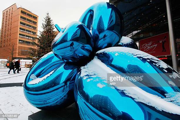 People walk past the snowcovered sculpture 'Balloon Flower' by US artist Jeff Koons at Berlin's Potsdamer Platz on December 18 2009 More snowfall and...