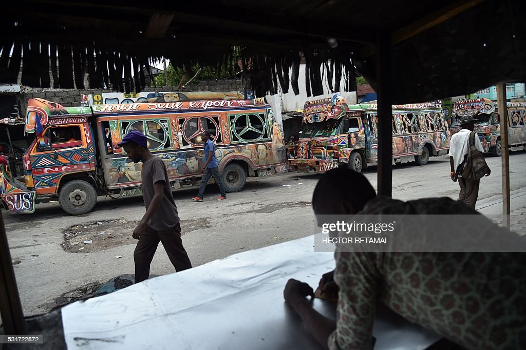People walk past the stop of Tap Tap, public transportation vehicles, in Port-au-Prince on May 27, 2016. / AFP / HECTOR