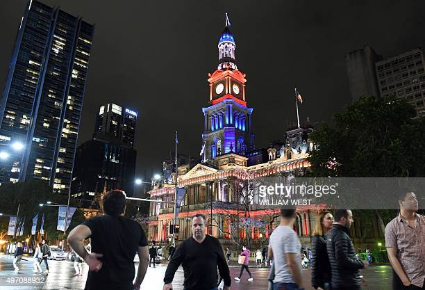 People walk past the Sydney Town Hall as it is lit in red white and blue resembling the colours of the French flag in Sydney on November 14 as...