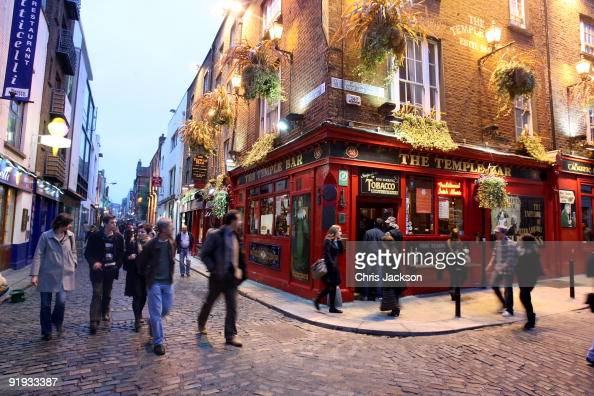 People walk past the Temple Bar pub in Temple Bar on October 15 2009 in Dublin Ireland Dublin is Ireland's capital city located near the midpoint of...