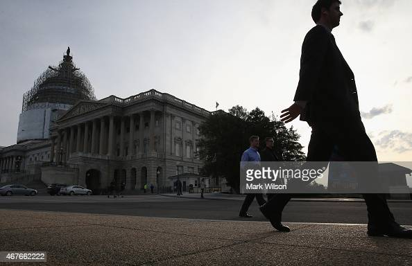 People walk past the US Capitol Building where the Senate is working late into the evening before leaving on a two week break March 26 2015 in...