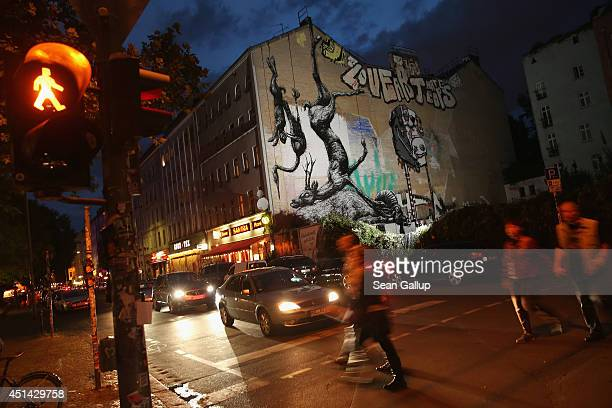 People walk past the work 'Animals' by street artist Roa in Kreuzberg district on June 26 2014 in Berlin Germany Berlin with its long tradition of...