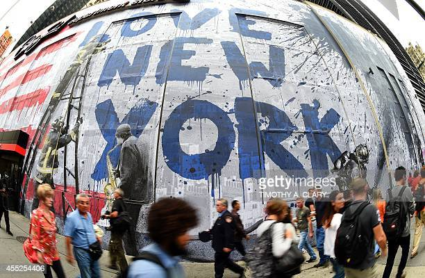People walk past the work of artist Mr Brainwash as he creates a massive 9/11 Mural on the side of Century 21 across the street from the The National...