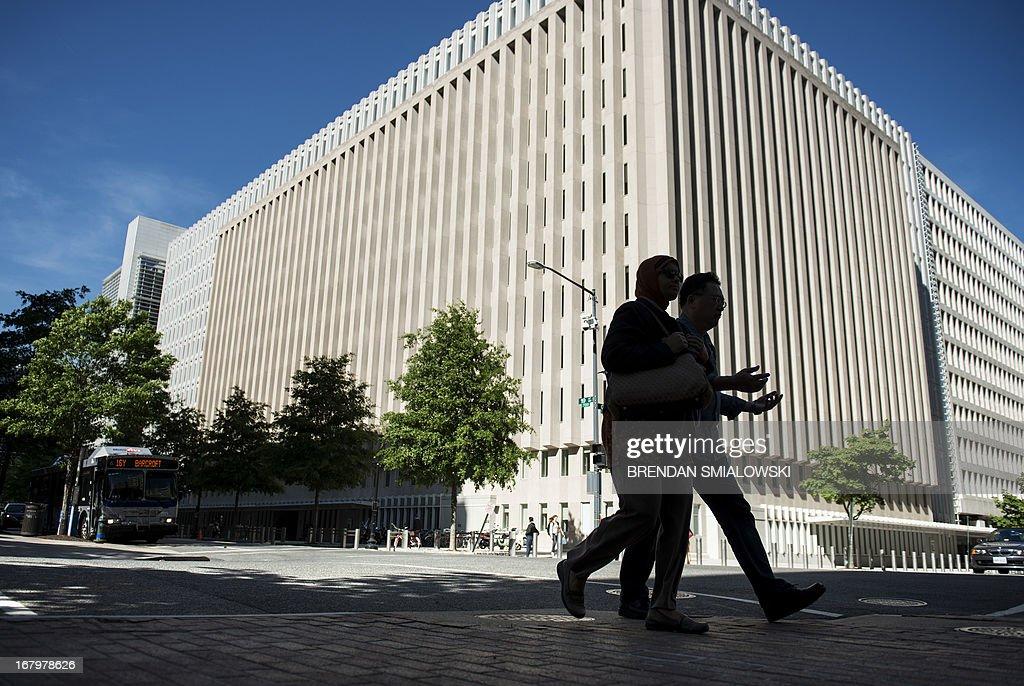 People walk past the World Bank Group's headquarters May 3, 2013 in Washington, DC. AFP PHOTO/Brendan SMIALOWSKI