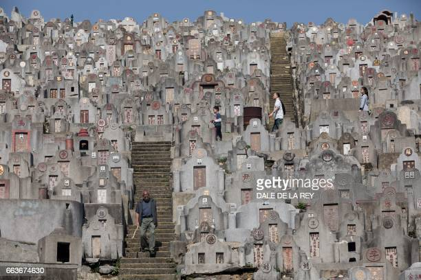 People walk past tombstones at a cemetery ahead of the Ching Ming Festival or gravesweeping day in Hong Kong on April 2 2017 Visiting the graves of...
