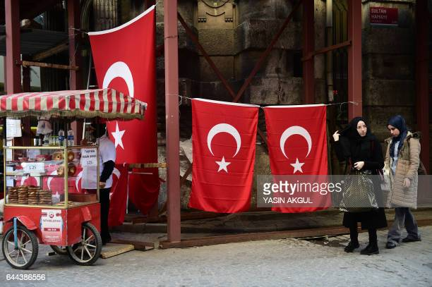 People walk past Turkish national flags as a street vendor sells Turkish traditional backery in the Eminonu district of Istanbul on February 23 2017...