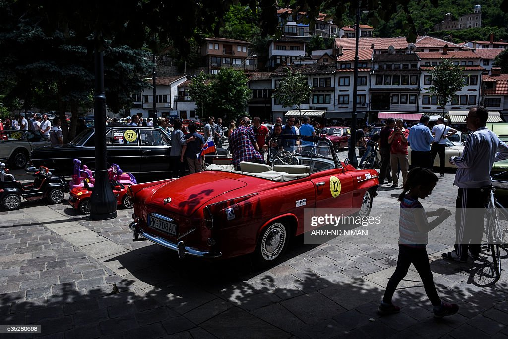 People walk past vintage cars displayed during the 11th Old Timers Fest on May 29, 2016 in Prizren. / AFP / ARMEND
