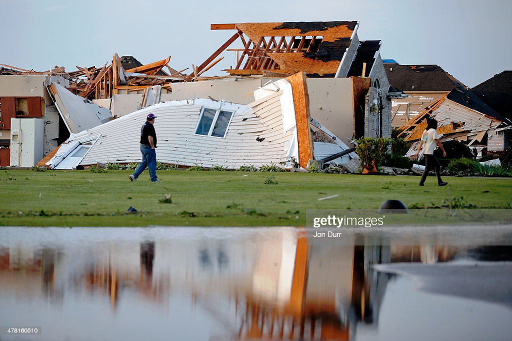 People walk past wreckage near Elizabeth Drive and Coaler Drive after a tornado struck the previous day on June 23 2015 in Coal City Illinois
