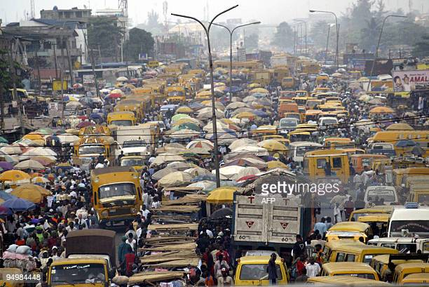 People walk struggling for space between public transport buses and trucks at the burstling Oshodi bus stop in Lagos 06 February 2006 Lagos is...