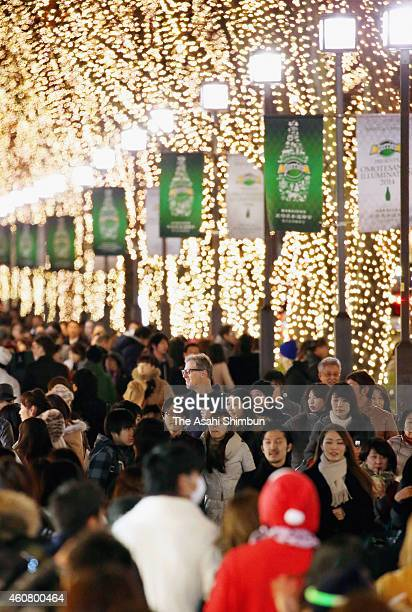 People walk the illuminated Omotesando on December 23 2014 in Tokyo Japan
