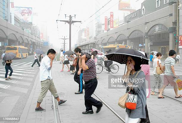 People walk the volcanic ash covered citycenter on a day of Mt Sakurajima eruption on August 18 2013 in Kagoshima Japan The Japan Meteorological...
